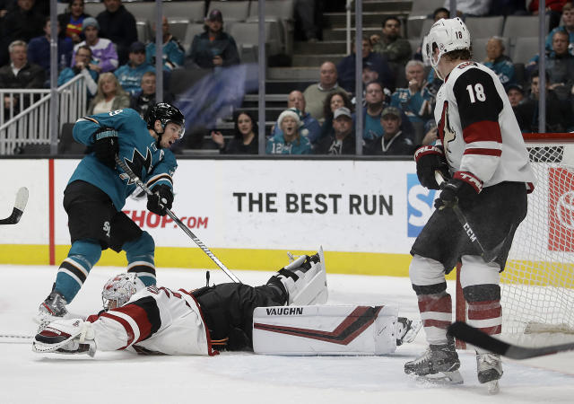 Arizona Coyotes goalie Darcy Kuemper (35) slides on the ice to block a shot from San Jose Sharks' Logan Couture, left, during the first period of an NHL hockey game Tuesday, Dec. 17, 2019, in San Jose, Calif. At right is Arizona's Christian Dvorak (18). (AP Photo/Ben Margot)