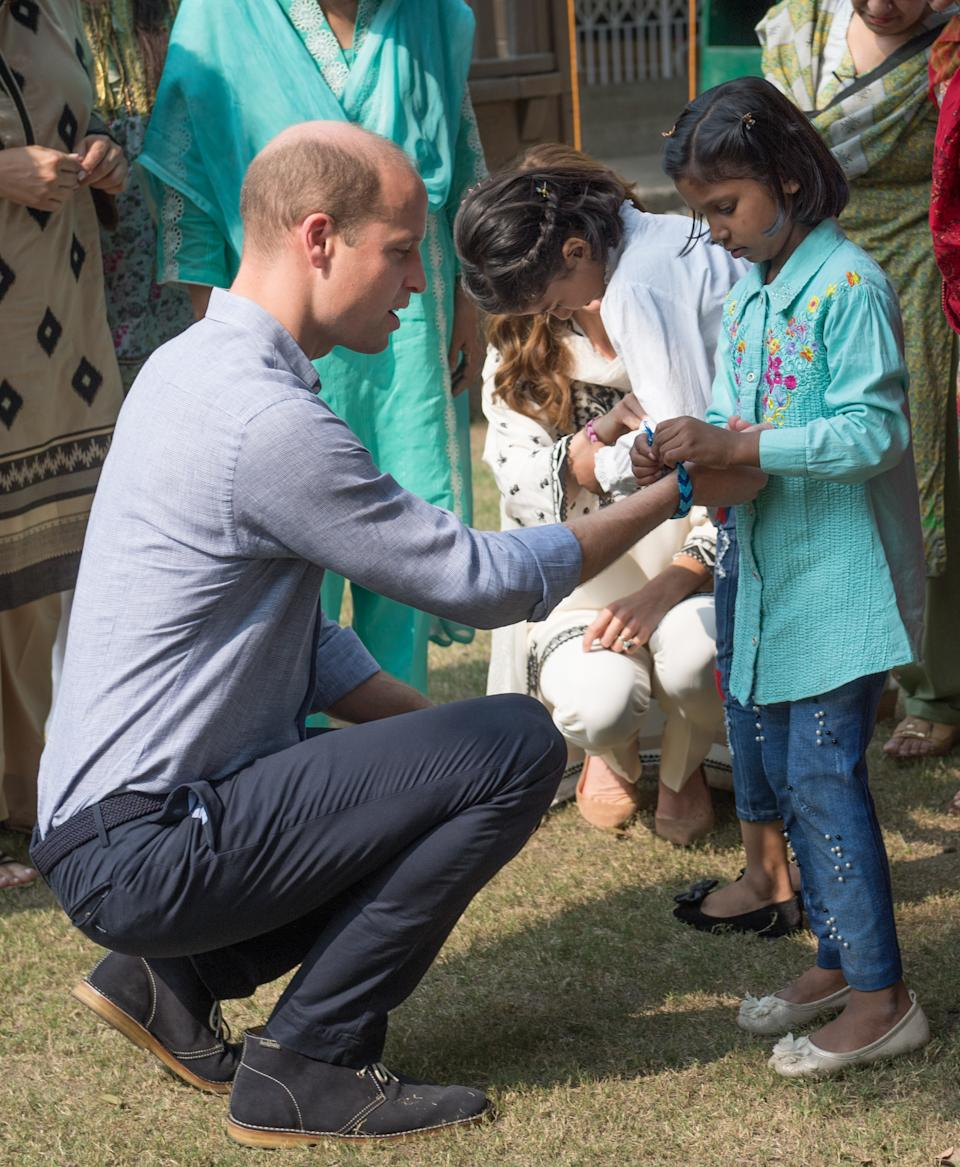 LAHORE, PAKISTAN - OCTOBER 18: Prince William, Duke of Cambridge is given a bracelet by children as he visits SOS Children's Village, a charitable organisation in the heart of the city, on October 18, 2019 in Lahore, Pakistan. (Photo by Samir Hussein/WireImage)