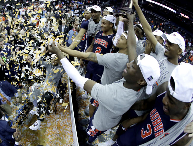 Auburn players celebrate with injured teammate Chuma Okeke, left, after the Midwest Regional final game against Kentucky in the NCAA men's College basketball tournament Sunday, March 31, 2019, in Kansas City, Mo. Auburn won 77-71 in overtime. (AP Photo/Charlie Riedel)