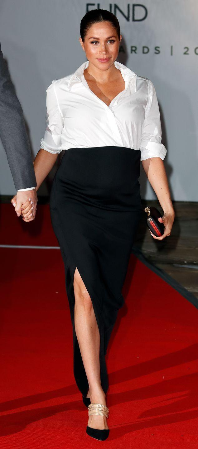<p>Meghan Markle tucked a crisp white Givenchy button-down into a black floor-length pencil skirt back in 2019. The Duchess' sophisticated look was for the Endeavor Fund Awards in London. </p>