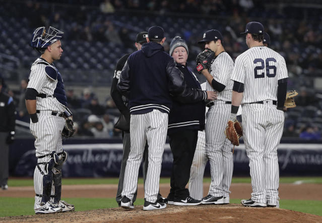 New York Yankees head trainer Steve Donohue, center, talks with manager Aaron Boone as he checks pitcher Luis Cessa on the mound during the eighth inning of a baseball game against the Miami Marlins, Tuesday, April 17, 2018, in New York. Cessa was pulled from the game. (AP Photo/Julie Jacobson)