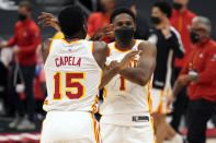 Atlanta Hawks center Clint Capela (15) and forward Nathan Knight (1) celebrate their win over the Toronto Raptors during an NBA basketball game Tuesday, April 13, 2021, in Tampa, Fla. (AP Photo/Chris O'Meara)