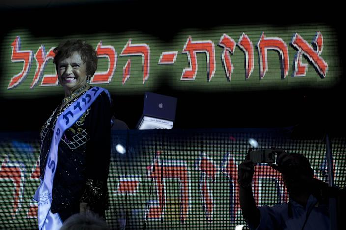 """Mania Herman, a Holocaust survivor participates in a beauty pageant, in the northern Israeli city of Haifa, Thursday, June 28, 2012. Fourteen women who lived through the horrors of World War II paraded on stage Thursday night in an unusual pageant, vying for the honor of being Israel's first """"Miss Holocaust Survivor."""" (AP Photo/Sebastian Scheiner)"""