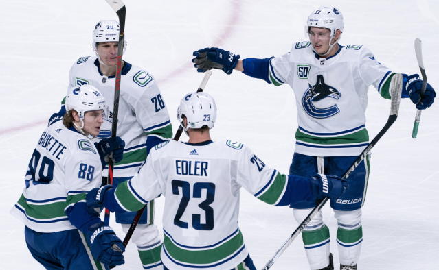 Vancouver Canucks' Alexander Edler is congratulated for his goal against the Montreal Canadiens by teammates Adam Gaudette, Antoine Roussel and Troy Stecher, left to right, during the second period of an NHL hockey game Tuesday, Feb. 25, 2020, in Montreal. (Paul Chiasson/The Canadian Press via AP)
