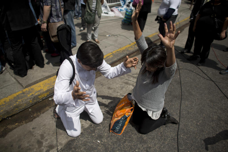 Supporters of Argentina's President Cristina Fernandez pray outside the Favaloro Hospital in Buenos Aires, Argentina, Wednesday, Oct. 9, 2013. The doctors who removed a blood clot from the brain of Argentina's president on Tuesday say she's improving without complications. (AP Photo/Victor R. Caivano)