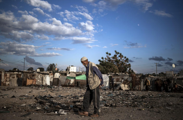 A Palestinian elderly man walks in a slum on the outskirts of Khan Younis Refugee Camp, in the southern Gaza Strip, Wednesday, Nov. 25, 2020. Israel's blockade of the Hamas-ruled Gaza Strip has cost the seaside territory as much as $16.7 billion in economic losses and caused its poverty and unemployment rates to skyrocket, a U.N. report said Wednesday, as it called on Israel to lift the 13-year closure. (AP Photo/Khalil Hamra)