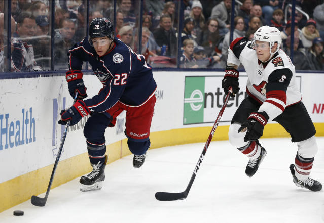 Columbus Blue Jackets' Sonny Milano, left, looks to pass the puck as Arizona Coyotes' Jakob Chychrun defends during the second period of an NHL hockey game Tuesday, Dec. 3, 2019, in Columbus, Ohio. (AP Photo/Jay LaPrete)