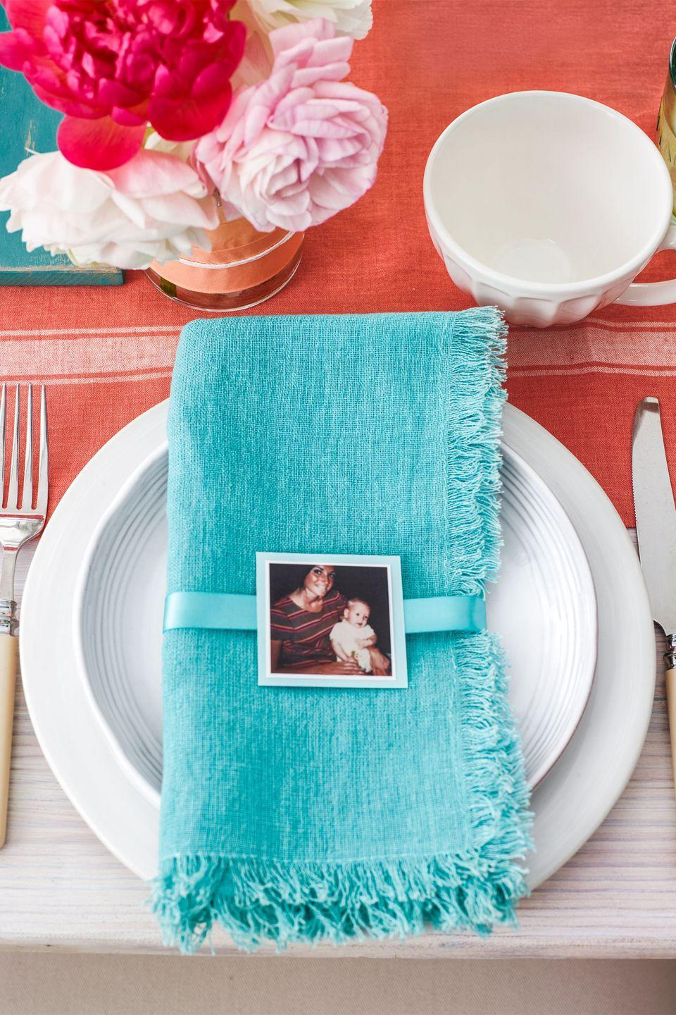 """<p>To make these sweet place cards for your <span class=""""redactor-unlink""""><a href=""""https://www.womansday.com/food-recipes/g2237/brunch-recipes/"""" rel=""""nofollow noopener"""" target=""""_blank"""" data-ylk=""""slk:Mother's Day brunch"""" class=""""link rapid-noclick-resp"""">Mother's Day brunch</a></span>, print an adorable old photo of you and mom, back it with card stock, and add a ribbon.</p>"""
