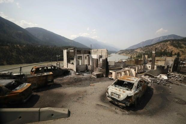 Damaged structures and vehicles are seen in Lytton, B.C., on Friday, after a wildfire destroyed most of the village on June 30.  (Darryl Dyck/The Canadian Press - image credit)