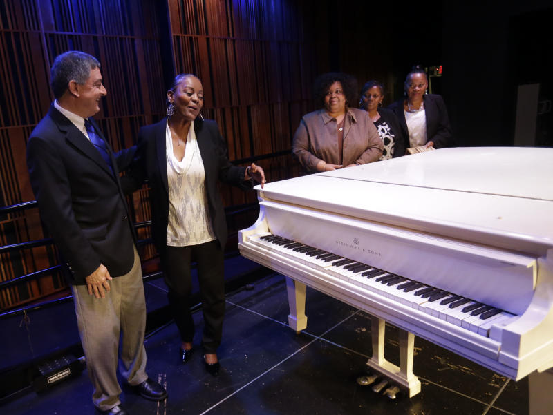 Louisiana Lt. Gov. Jay Dardenne, left, shows off a white Steinway grand piano, salvaged from the flooded Lower 9th Ward home of legendary musician Fats Domino after Hurricane Katrina, after being restored in New Orleans, Thursday, May 2, 2013. With him are Domino's daughters, left to right, Andrea Brimmer, Antoinette Smith, Anola Hartzog, and Adonica Domino. Its restoration came through $30,000 donated to the Louisiana Museum Foundation, and will be the centerpiece of an exhibit in the French Quarter.  (AP Photo/Gerald Herbert)
