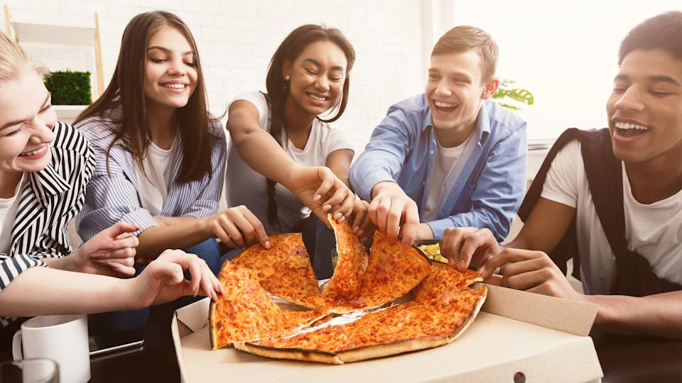 Time for snack. Happy students eating pizza and chatting at home