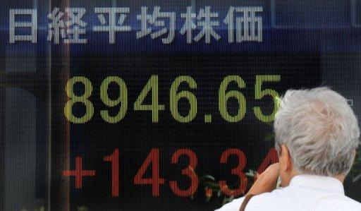 A man looks at a stock market information board in front of a securities company in Tokyo. Asian shares were mixed Tuesday as fears about the eurozone and a slowdown in China were offset by hopes the US central bank chief would this week outline steps to boost the world's biggest economy