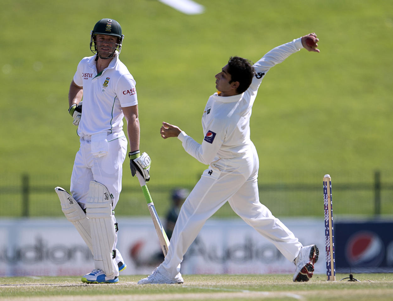 Pakistan's Saeed Ajmal bows as South Africa's batsman Ab de Villiers watches on the fourth day of their first Test against South Africa at the Sheikh Zayed Cricket Stadium in Abu Dhabi on October 17, 2013. AB de Villiers hit a fighting fifty to delay Pakistan's victory march over South Africa on the fourth day of the first Test in Abu Dhabi today. AFP PHOTO/STR        (Photo credit should read STR/AFP/Getty Images)