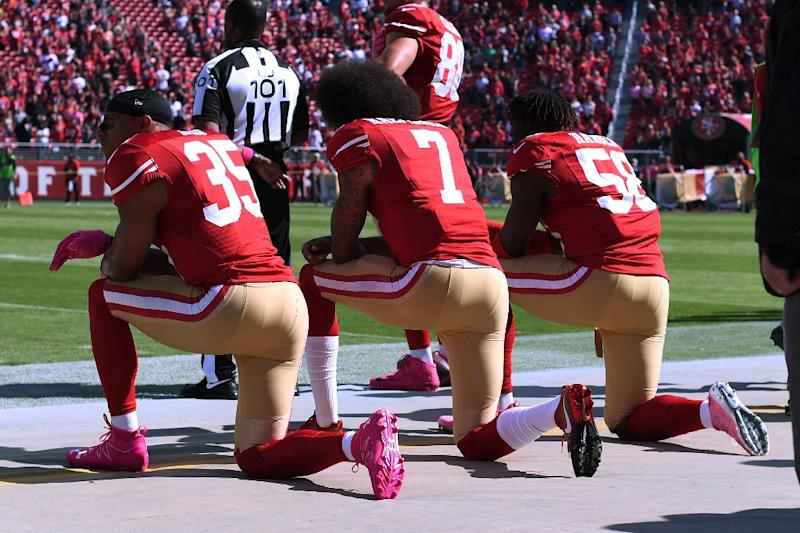 Colin Kaepernick (C), pictured in 2016 with teammates Eric Reid (L) and Eli Harold of the San Francisco 49ers, was one of a number of players who knelt in protest during the national anthem prior to NFL games, drawing the ire of President Trump (AFP Photo/Thearon W. HENDERSON)