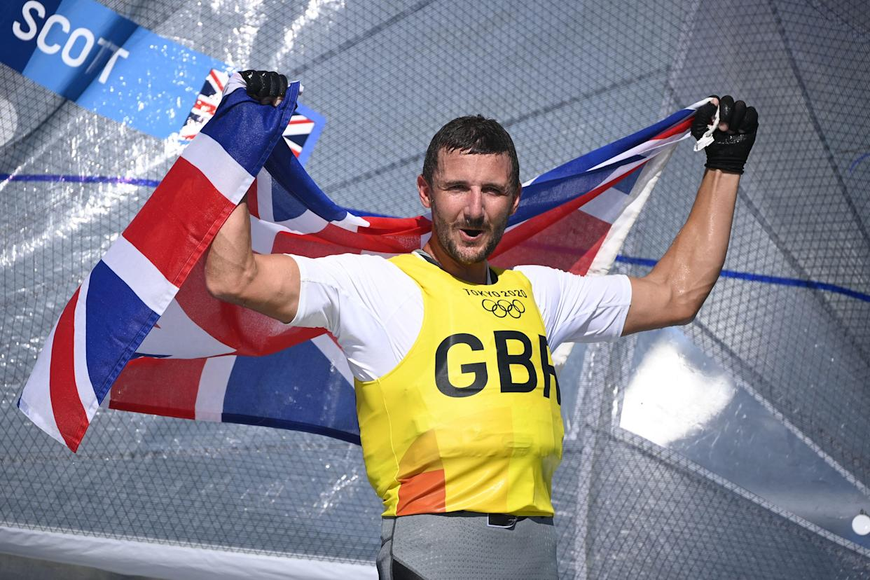 Great Britain's Giles Scott celebrates after the men's one-person dinghy (heavyweight) finn race during the Tokyo 2020 Olympic Games sailing competition at the Enoshima Yacht Harbour in Fujisawa, Kanagawa Prefecture, Japan, on August 3, 2021. (Photo by Olivier MORIN / AFP) (Photo by OLIVIER MORIN/AFP via Getty Images)