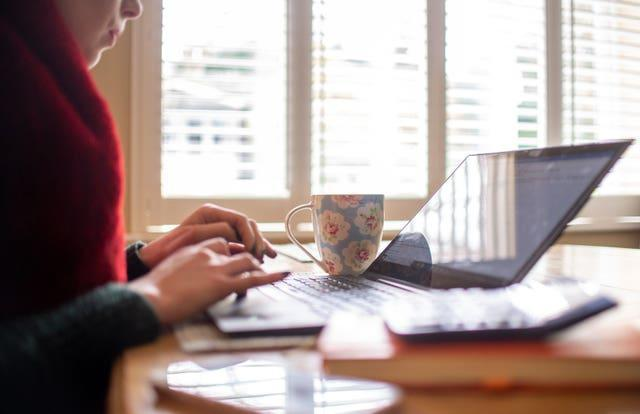 A woman using a laptop on a dining room table