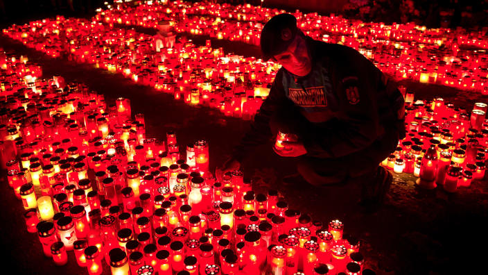 """FILE - In this Monday, Nov. 2, 2015 photograph, a riot policeman places a candle, collected from people waiting to pay respects to the victims of a fire, outside the Colectiv nightclub, in Bucharest, Romania. The Oscar-nominated Romanian documentary film """"Collective"""" follows a group of journalists delving into the state of health care in the eastern European country in the wake of a deadly 2015 nightclub fire that left dozens of burned victims in need of complex treatment. What they revealed was decades of deep-rooted corruption, a heavily politicized system scarily lacking in care. (AP Photo/Vadim Ghirda, File)"""