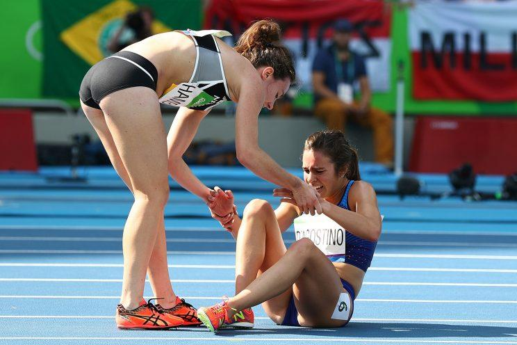 Abbey D'Agostino (R) is assisted by Nikki Hamblin of New Zealand. (Getty)