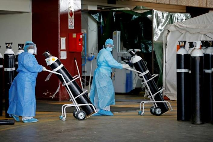South Africa has been badly hit by coronavirus. At the Steve Biko Academic Hospital in Pretoria, health workers take oxygen tanks into a temporary ward for Covid patients