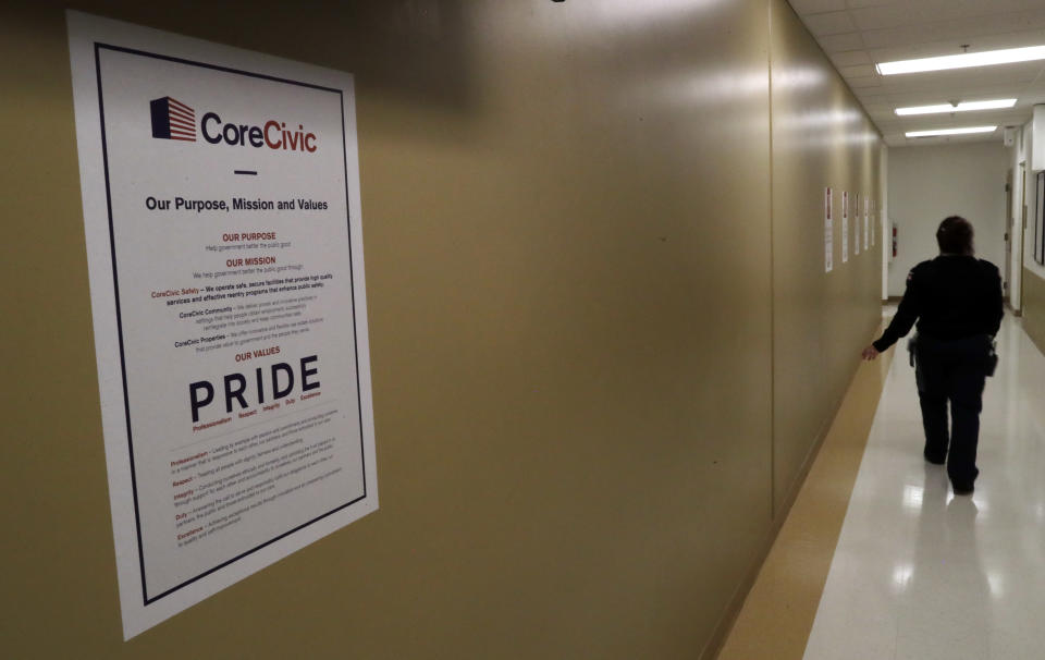 A guard passes a sign for CoreCivic at the Otay Mesa Detention Center Wednesday, Aug. 23, 2017, in San Diego. The facility was at the center of the first big novel coronavirus outbreak at a U.S. immigration detention center in April 2020. (AP Photo/Gregory Bull)