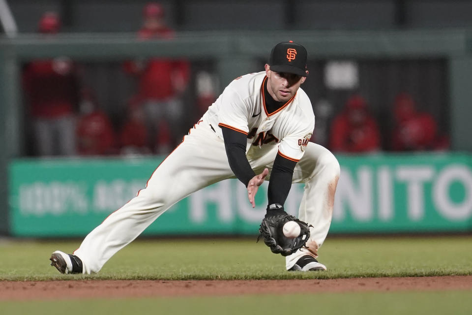 San Francisco Giants second baseman Tommy La Stella fields a grounder by Cincinnati Reds' Eugenio Suarez, who was out at first during the sixth inning of a baseball game in San Francisco, Tuesday, April 13, 2021. (AP Photo/Jeff Chiu)