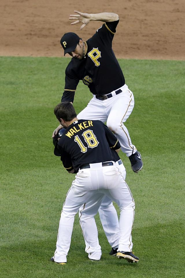 Pittsburgh Pirates' Garrett Jones, top, and Neal Walker (18) tackle teammate Alex Presley, rear, after driving in the game-winning run with a single off St. Louis Cardinals relief pitcher Kevin Siegrist in the 11th inning of the first baseball game of a double header in Pittsburgh, Tuesday, July 30, 2013. The Pirates won 2-1 in 11 innings. (AP Photo/Gene J. Puskar)
