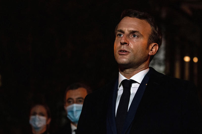 French President Emmanuel Macron speaks in front of a high school Friday Oct.16, 2020 in Conflans Sainte-Honorine, northwest of Paris, where a history teacher who opened a discussion with high school students on caricatures of Islam's Prophet Muhammad was beheaded.