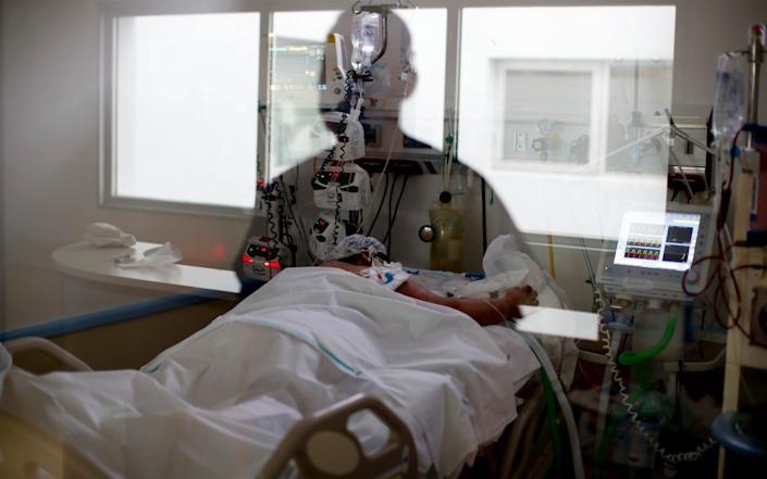 An intensive care unit nurse, reflected in a window, looks in on a Covid-19 patient, at the El Cruce Dr. Nestor Carlos Kirchner Hospital, on the outskirts of Buenos Aires - AP