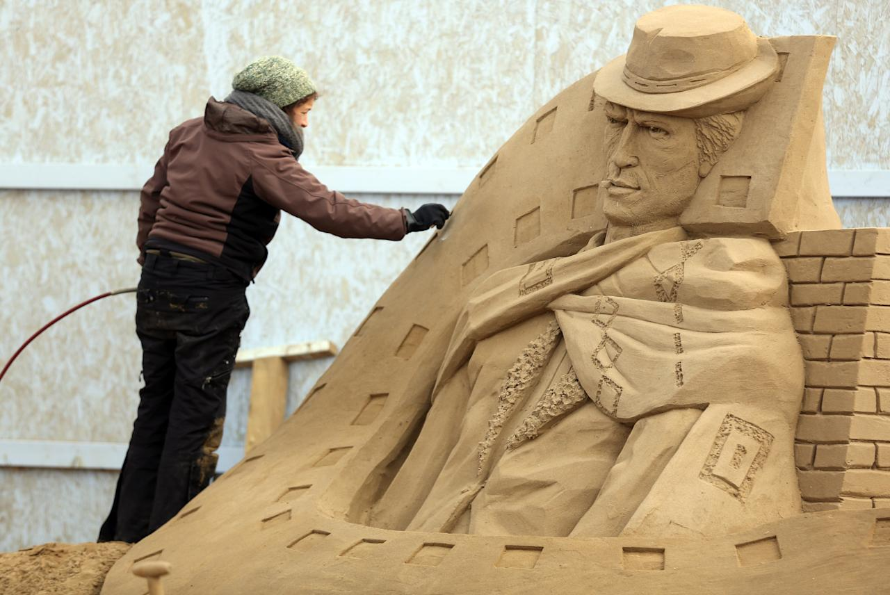 WESTON-SUPER-MARE, ENGLAND - MARCH 26:  A sand sculptor works on a Clint Eastwood sand sculpture as pieces are prepared as part of this year's Hollywood themed annual Weston-super-Mare Sand Sculpture festival on March 26, 2013 in Weston-Super-Mare, England. Due to open on Good Friday, currently twenty award winning sand sculptors from across the globe are working to create sand sculptures including Harry Potter, Marilyn Monroe and characters from the Star Wars films as part of the town's very own movie themed festival on the beach.  (Photo by Matt Cardy/Getty Images)