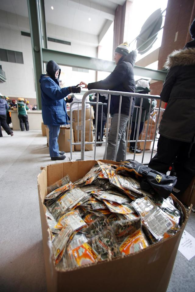 Fans receive free hand warmers as they arrive at Lambeau Field for an NFL wild-card playoff football game between the Green Bay Packers and the San Francisco 49ers, Sunday, Jan. 5, 2014, in Green Bay, Wis. (AP Photo/Jeffrey Phelps)