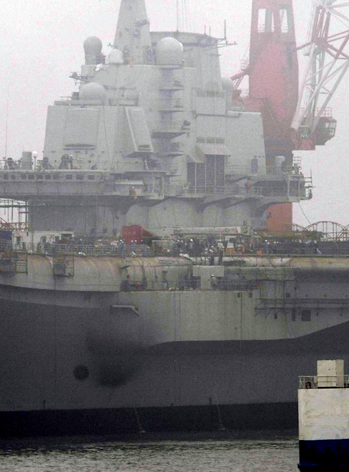 """China's first aircraft carrier, former """"Varyag"""" of Ukraine, is under restoration in a shipyard in Dalian in northeastern China's Liaoning province, in the foggy morning on Friday, July 1, 2011. Blinking light apparently from welding arc were seen on the deck and crane operations continued in the morning, Japan's Kyodo News said. (AP Photo/Kyodo News) JAPAN OUT, MANDATORY CREDIT, NO LICENSING IN CHINA, FRANCE, HONG KONG, JAPAN AND SOUTH KOREA"""