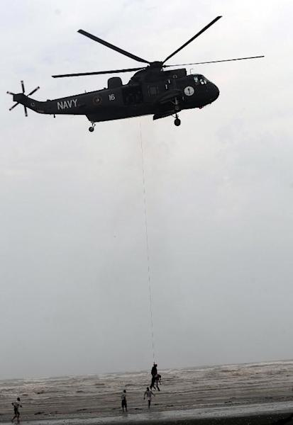 A Pakistan Navy rescuer, hanging from the winch line of a Sea King helicopter, recovers the body of a drowning victim over Clifton beach in Karachi on August 1, 2014