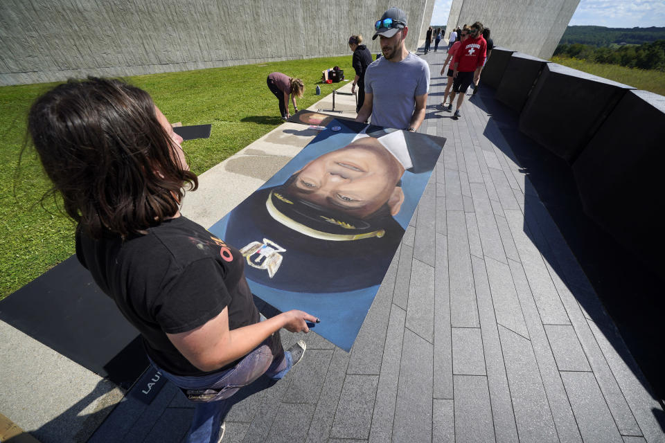 Chalk artist Naomi Haverland, from Orlando Fla., left, helps move a chalk portrait of Flight 93 Captain Jason M. Dahl, of Littleton, Colo., along the flight path take by Flight 93 that leads to the Flight 93 National Memorial on Thursday, Sept. 9, 2021, in Shanksville, Pa., as the nation prepares to mark the 20th anniversary of the Sept. 11, 2001 attacks, Saturday, Sept. 11, 2021. A group of 11 chalk artists from around the country worked for two days on the portraits of the forty passengers and crew who perished in the crash of Flight 93 on Sept. 11, 2001. (AP Photo/Gene J. Puskar)