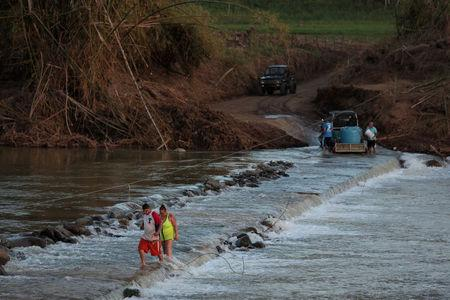 Local residents cross a river using a cable after Hurricane Maria destroyed the town's bridge in San Lorenzo, Morovis, Puerto Rico, October 4, 2017. REUTERS/Alvin Baez