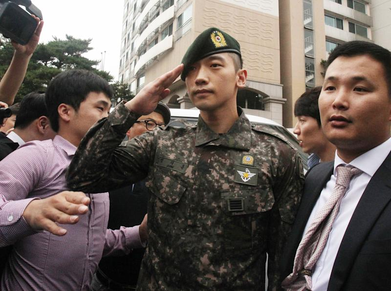 South Korean actor and singer Rain, center, salutes to his fans and media after he served 21 months in the army in front of the Defense Ministry in Seoul, South Korea, Wednesday, July 10, 2103. (AP Photo/Ahn Young-joon)