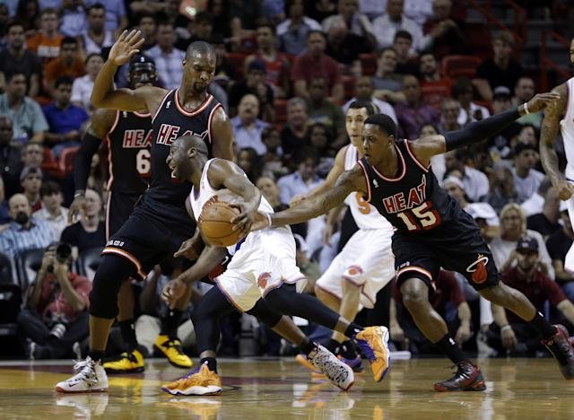 New York Knicks point guard Raymond Felton, center, drives against Miami Heat center Chris Bosh (1) as Heat's Mario Chalmers (15) defends during the first half of an NBA basketball game in Miami, Thursday, Feb. 27, 2014. (AP Photo/Alan Diaz)