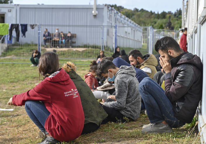 Migrants sit in front of containers at the Central Initial Reception Facility for Asylum Seekers, ZABH, in the federal German state of Brandenburg in Eisenhuettenstadt, Germany, Wednesday, Oct. 6, 2021. German federal police said more than 4,300 people crossed the border from Poland 'illegally' this year. Most people are being put up at asylum centers in the eastern state of Brandenburg. (Patrick Pleul/dpa via AP)
