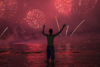 A man watches fireworks exploding over Copacabana Beach during the New Year's celebrations, in Rio de Janeiro, Brazil, Wednesday, Jan. 1, 2020. (AP Photo/Bruna Prado)