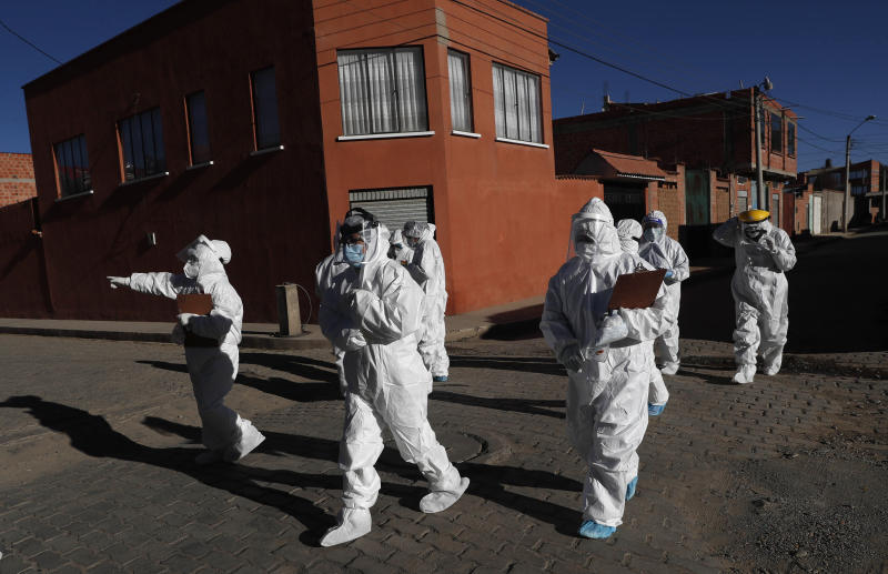 Dressed in full protective gear, doctors span out in a house-to-house new coronavirus testing campaign in the Villa Jaime Paz Zamora neighborhood of El Alto, Bolivia, Saturday, July 4, 2020. (AP Photo/Juan Karita)