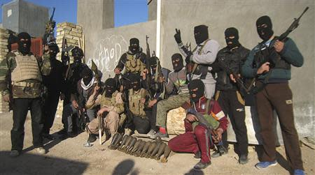Masked Sunni Muslim gunmen pose for a photo during a patrol in the city of Falluja, 70 km (44 miles) west of Baghdad, in this February 8, 2014 file photo. REUTERS/Stringer/Files