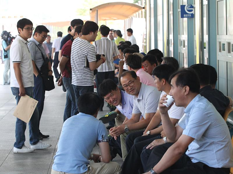 South Korean business men wait to leave for South and North Korea's joint Industrial Complex to conduct maintenance checks at their factories at Kaesong in North Korea, at the customs, immigration and quarantine office of the Inter-Korean Transit Office near the border village of Panmunjom, which has separated the two Koreas since the Korean War, in Paju, South Korea, Thursday, Aug. 22, 2013. North and South Korea on Aug. 14 moved closer to reopening the jointly run factory park, raising hopes for an improvement in ties between rivals that were trading war threats this spring. The development, while not conclusive, indicated progress after six failed rounds of talks, the last of which ended in a scuffle.(AP Photo/Ahn Young-joon)