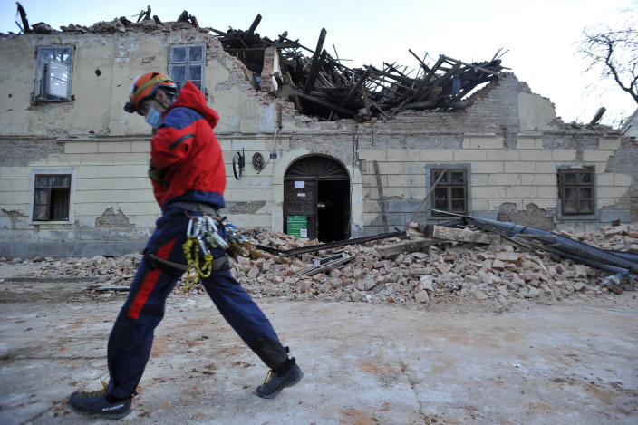 A rescuer walks past a building damaged in an earthquake in Petrinja, Croatia, Tuesday, Dec. 29, 2020. A strong earthquake has hit central Croatia and caused major damage and at least one death and some 20 injuries in the town southeast of the capital Zagreb. (AP Photo)