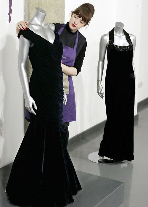 House assistant Lucy Bishop poses for a photograph with a Victor Edelstein velvet evening gown worn by Diana, Princess of Wales at Kerry Taylor Auctions in London March 1, 2013. The gown was worn by Diana to the state dinner at the White House given by U.S. President Ronald Reagan when she danced with actor John Travolta on November 9, 1985. The gown will be auctioned in London on March 19, 2013 and is expected to earn �200,000-�300,000 pounds (U.S. $300,560-450,864). REUTERS/Suzanne Plunkett