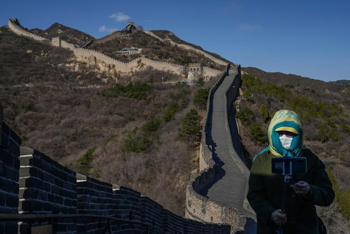 A woman wears a protective mask as she takes a photo on a nearly empty section of the Great Wall on March 27, 2020, near Badaling in Beijing, China.