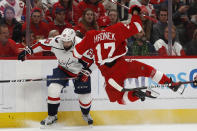 Washington Capitals defenseman Radko Gudas (33) checks Detroit Red Wings defenseman Filip Hronek (17) during the second period of an NHL hockey game Saturday, Nov. 30, 2019, in Detroit. (AP Photo/Carlos Osorio)
