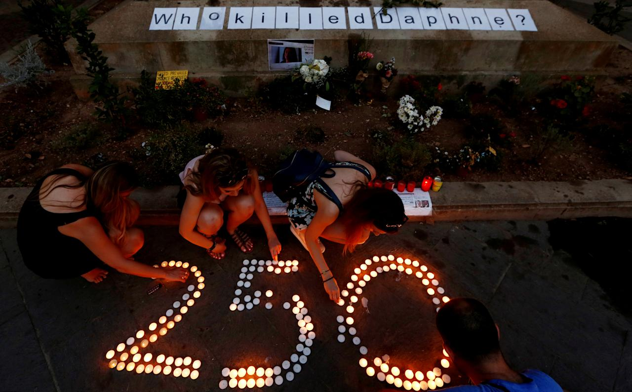 Greek and Italian tourists help a lone activist placing and lighting candles to mark 250 days since the assassination of anti-corruption journalist Daphne Caruana Galizia at a makeshift memorial to her outside the Courts of Justice in Valletta, Malta June 23, 2018. REUTERS/Darrin Zammit Lupi     TPX IMAGES OF THE DAY