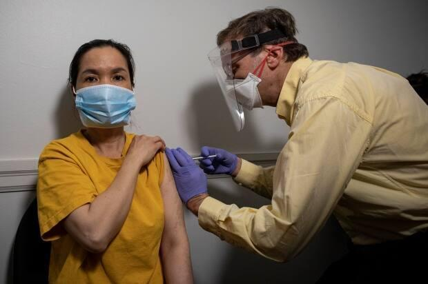 Thuy Vo gets her first dose of the Moderna COVID-19 vaccine during a door-to-door clinic for the residents of the San Romanoway apartments, in Toronto's northeast Jane and Finch neighbourhood. (Evan Mitsui/CBC - image credit)