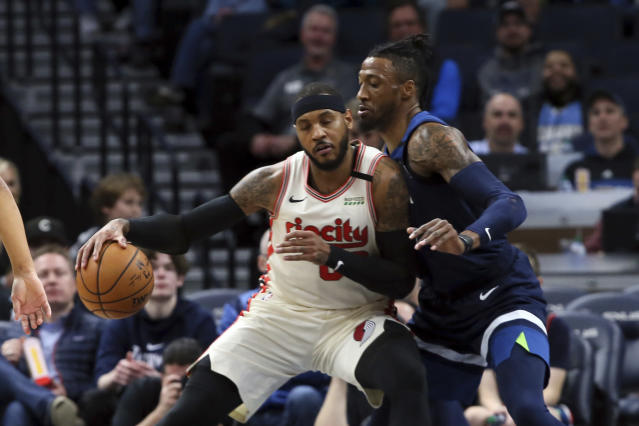 Portland Trail Blazers' Carmelo Anthony, left, drive as Minnesota Timberwolves' Robert Covington defends in the first half of an NBA basketball game Thursday, Jan. 9, 2020, in Minneapolis. (AP Photo/Jim Mone)