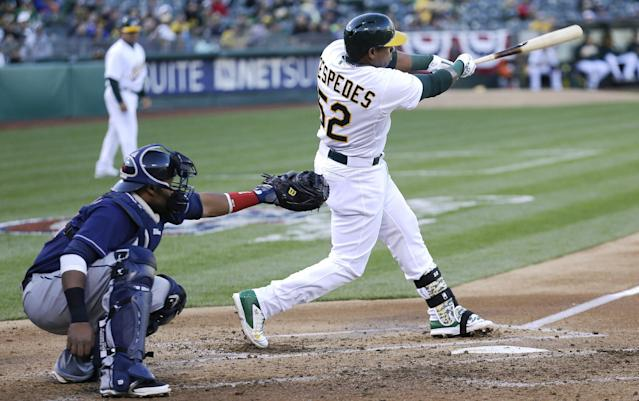 Oakland Athletics' Yoenis Cespedes (52) hits a double to score Jed Lowrie in front of Cleveland Indians third baseman Carlos Santana during the first inning of a baseball game in Oakland, Calif., Wednesday, April 2, 2014. (AP Photo/Jeff Chiu)