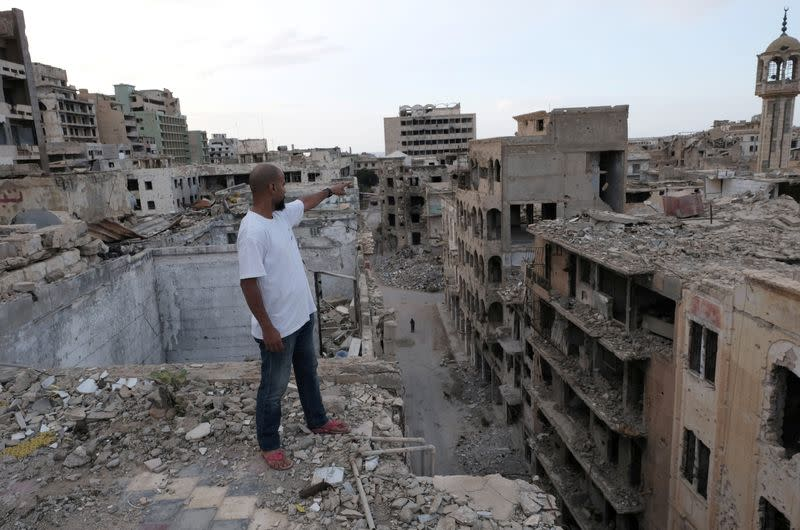 Malik Abdullah Ali reacts as he stands on the damaged roof of the building where he lives, in Benghazi